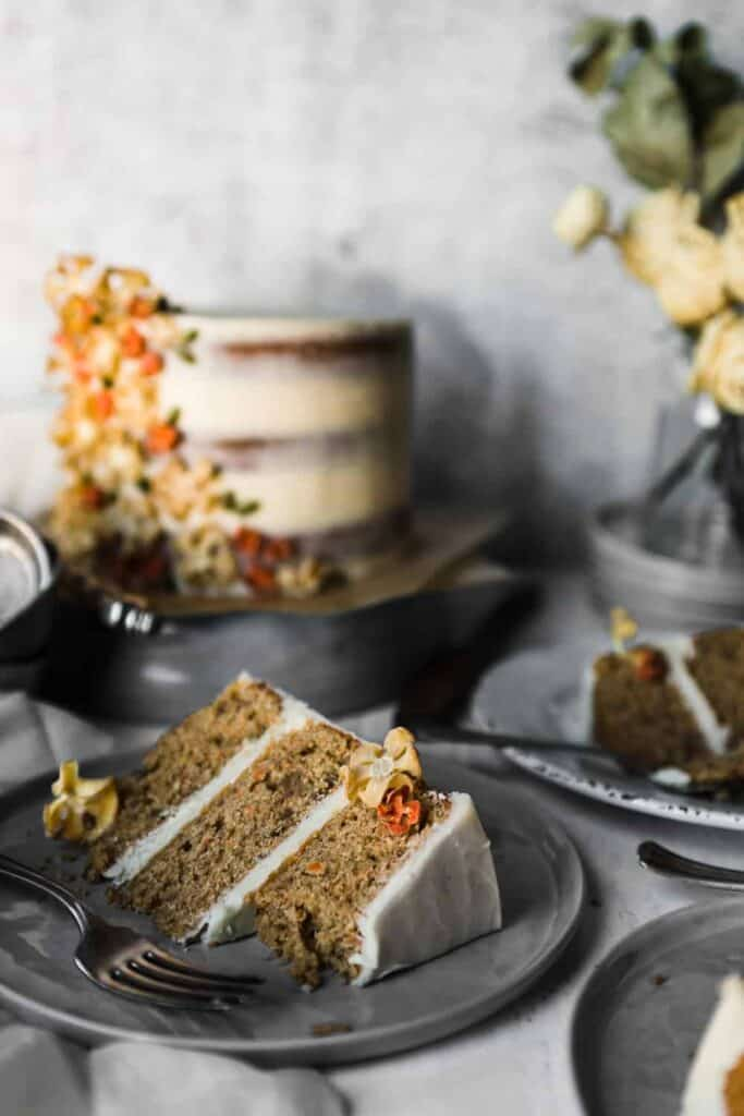 a slice of carrot spice cake on a plate garnished with dehydrated carrot flowers. More slices and the full carrot spice cake are in the background with a vase of dried roses