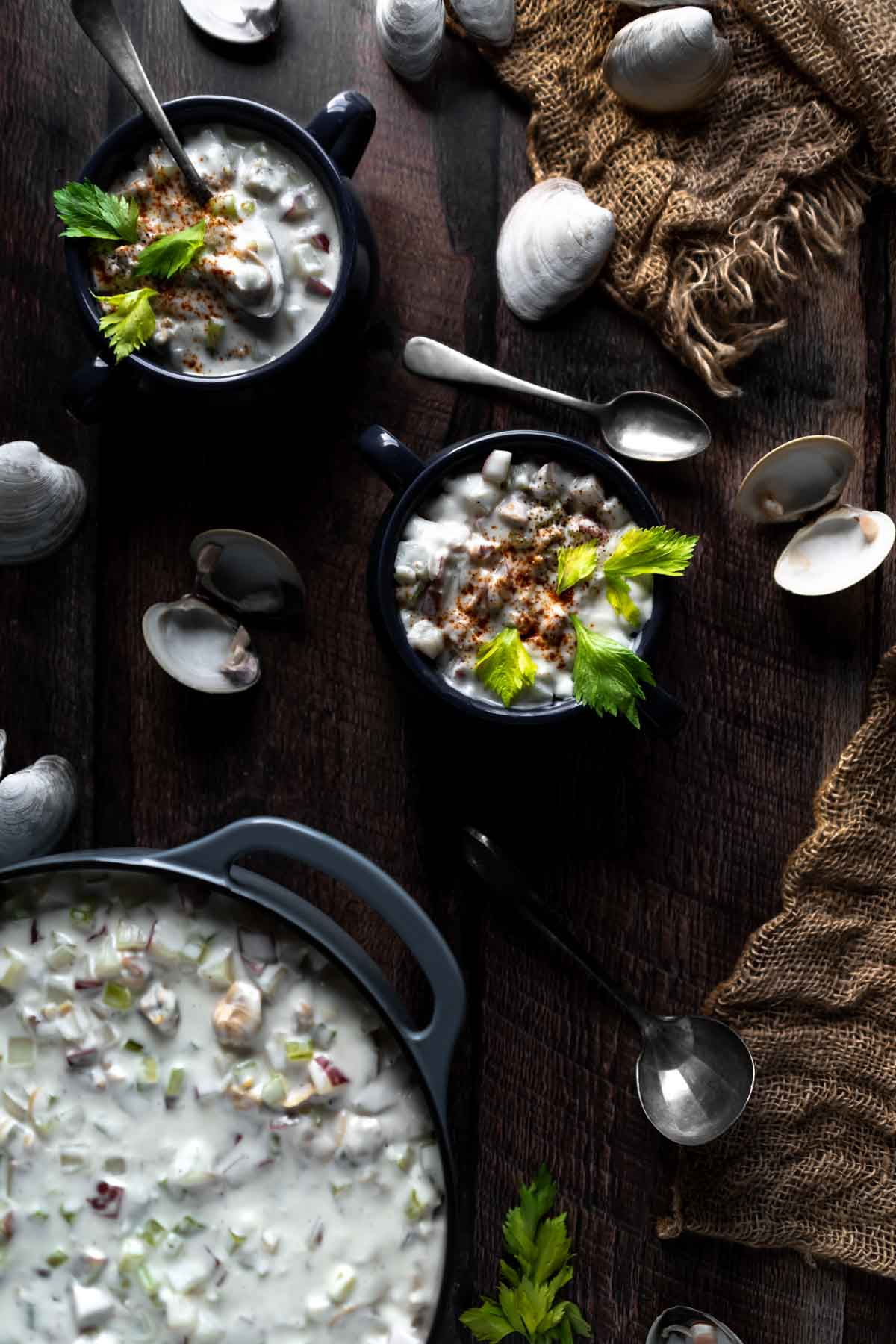 Flat Lay Photo of Chowder in a dutch oven and two bowls surrounded by Littleneck Clam Shells, spoons and a burlap net
