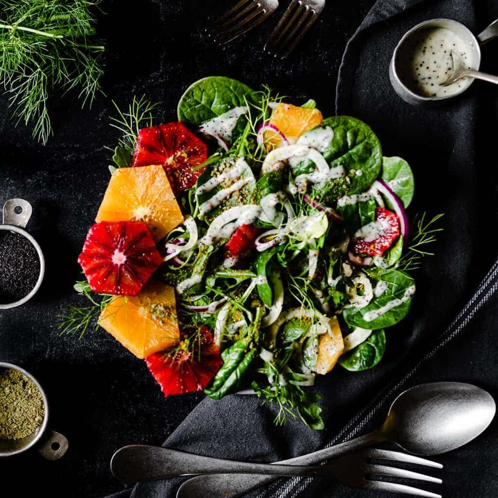 a big bowl of salad with alternating slices of orange and blood orange on one side and a drizzle of poppyseed dressing over the top. The salad is surrounded by cups of more dressing, pistachios, poppyseeds, serving utensils and fresh fennel fronds