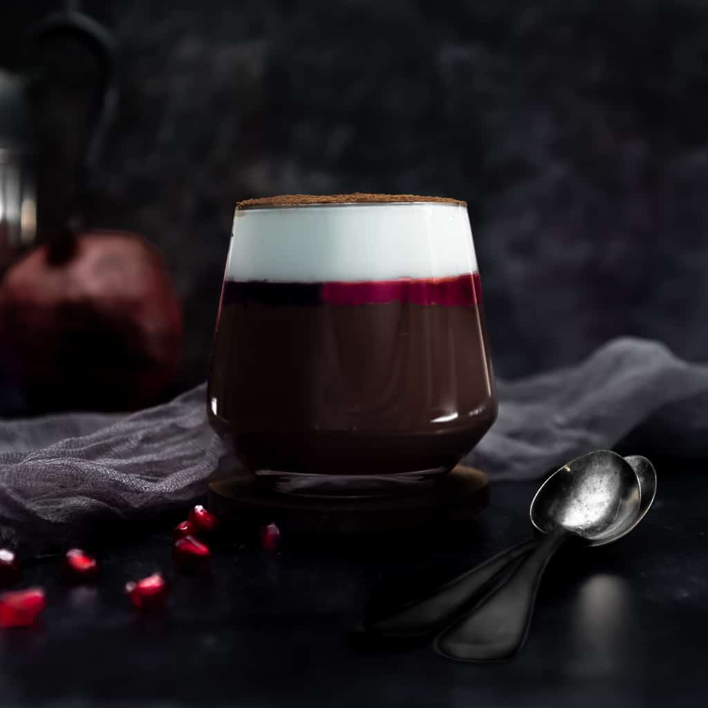 a glass filled with dark chocolate cremeaux topped with a thin layer of pomegranate gelee and a layer of whipped cream dusted in cocoa powder. The glass is next to a spoon and a sprinkle of pomegranate arils