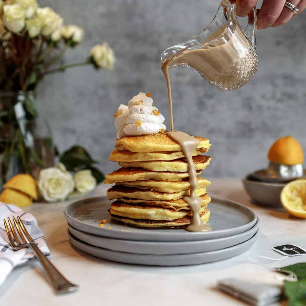 A tall stack of lemon pancakes topped with a swirl of whipped cream on a stack of grey plates surrounded by flowers and lemons. Earl grey creme anglaise is being poured over the pancakes from a crystal pourer.