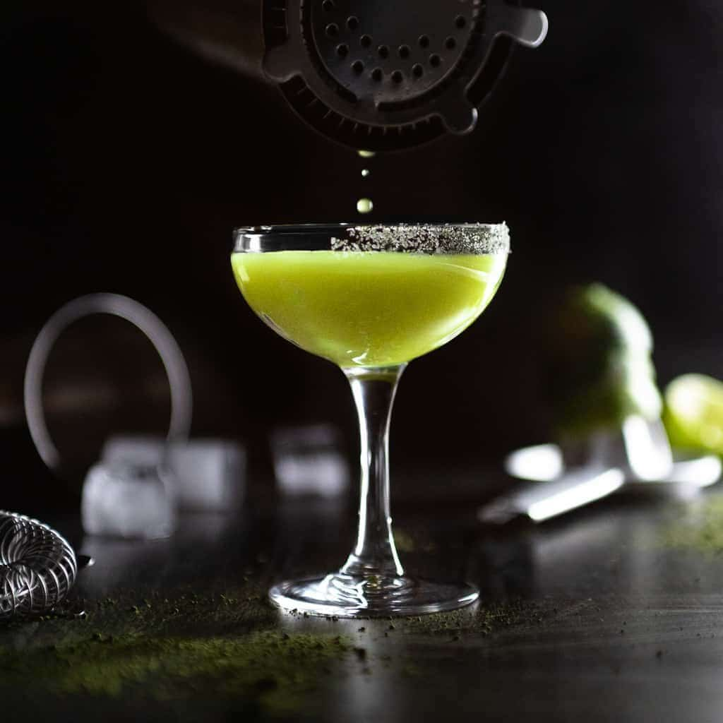 The last drops of a Matcha Margarita being poured from a cocktail shaped inso a coupe glass with a matcha salt rim