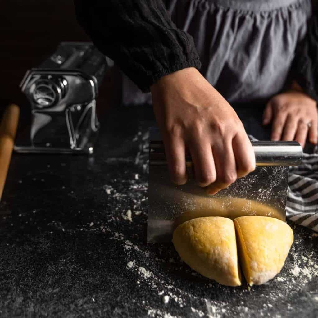 A woman cutting a ball of pasta dough into quarters with a bench scraper