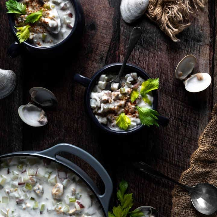 An overhead shot of two bowls of littleneck clam chowder next to clam shells, a burlap net and a blue dutch oven of more chowder