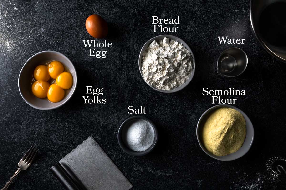 a picture of ingredients needed to make semolina pasta dough. In small bowls there are egg yolks, bread flour, semolina flour, water salt and a whole egg