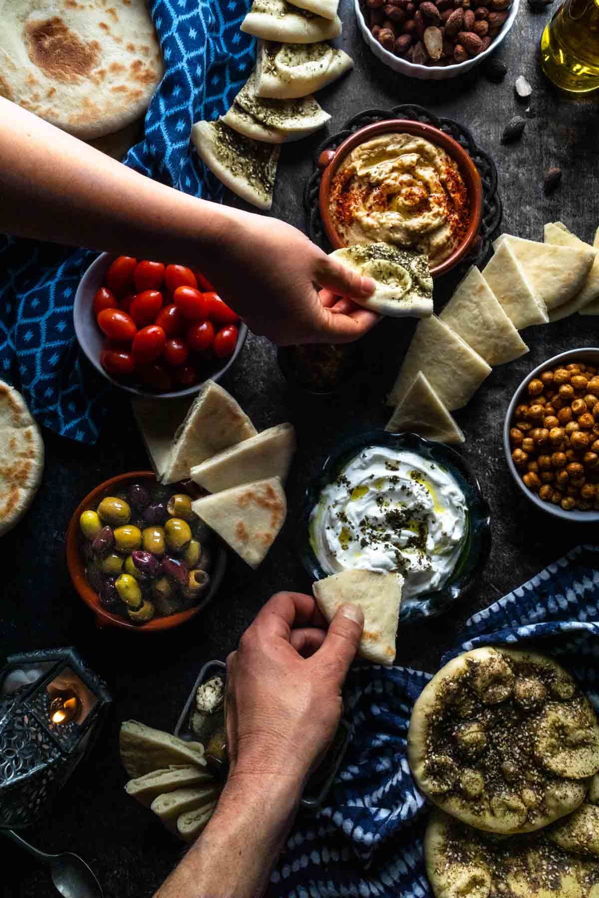An overhead photo of two hands dipping pita bread into a colrful assortment of mezze including hummus and tzatziki dips.