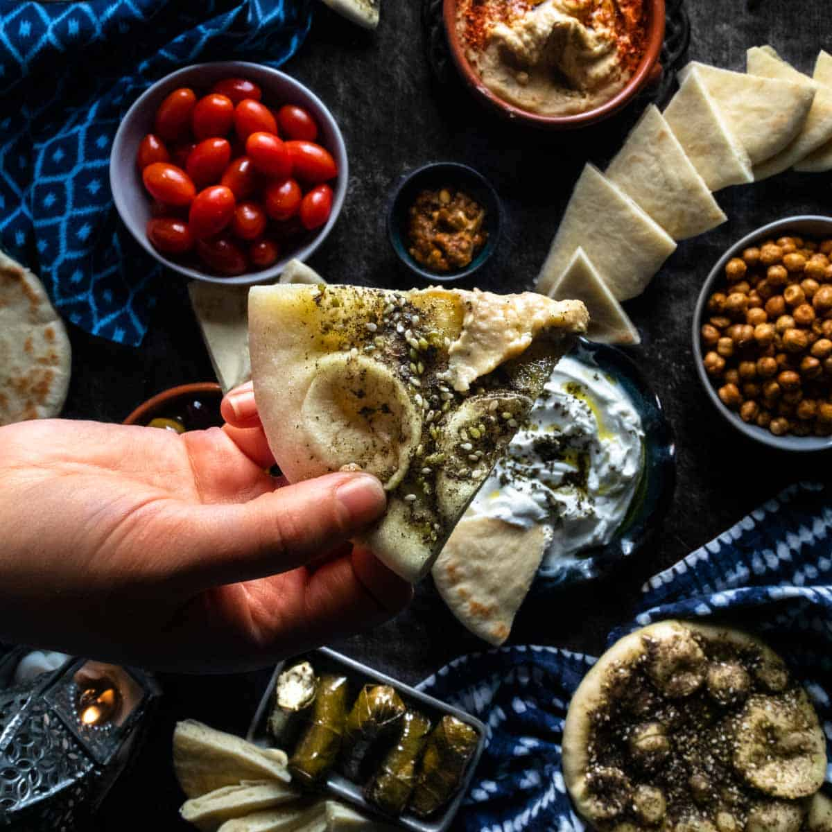 A triangle of za'atar spiced pita bread being held above a colorful spread of meze, olives, chickpeas and dolmas