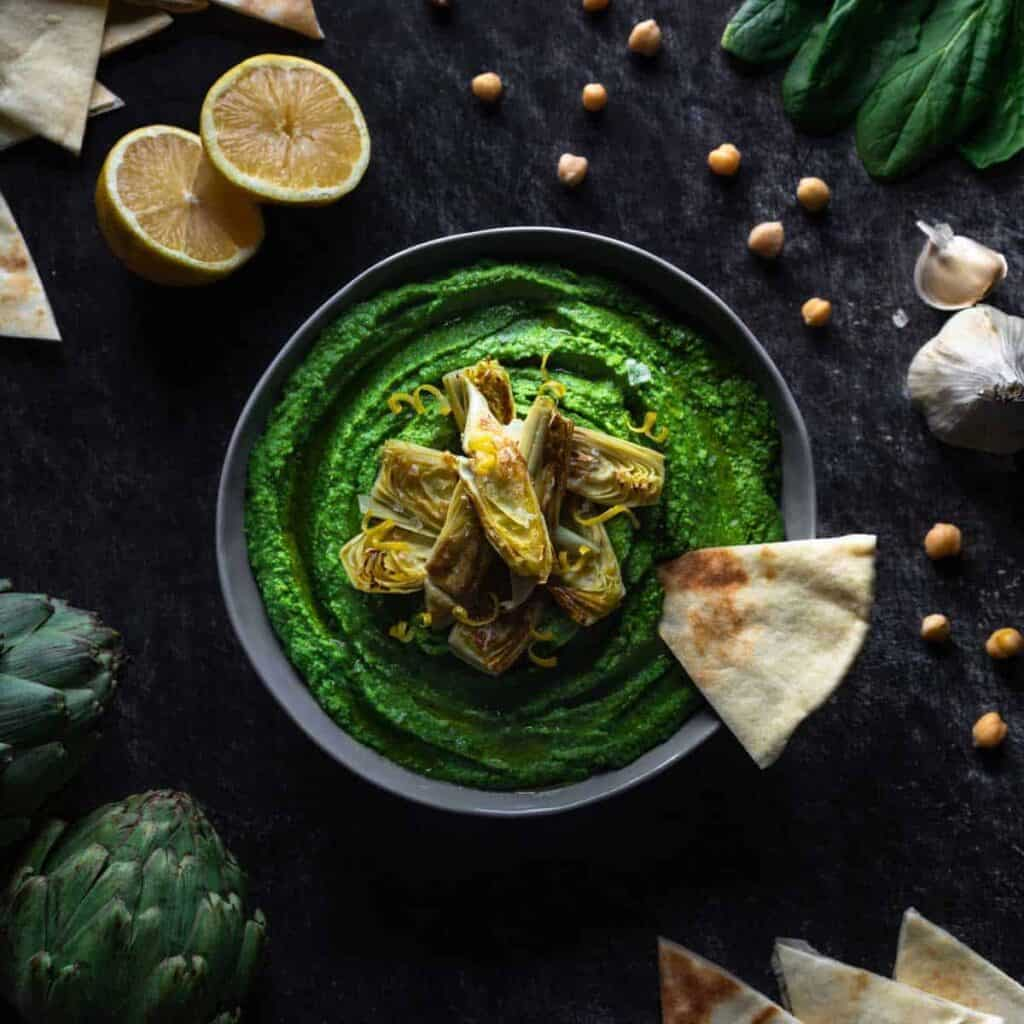 A pita triangle dipped into a bowl of spinach hummus topped with seared artichoke hearts and surrounded by chickpeas, artichokes, lemons, and more pita bread