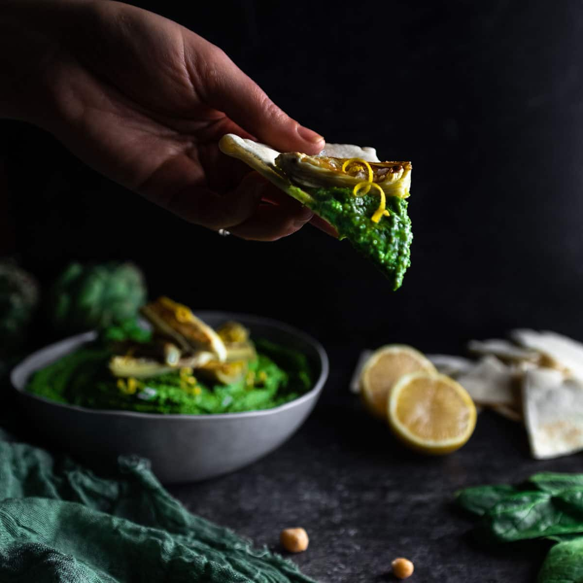 Lemon zest spiral garnishing a piece of pita bread topped with spinach hummus and an artichoke heart