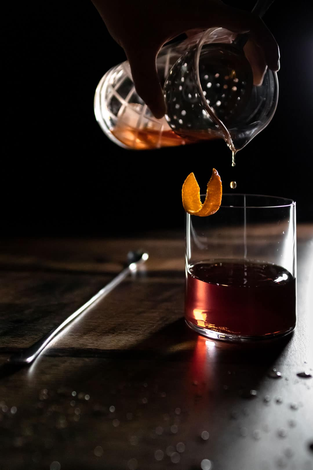 The last drops of a Cynar toronto cocktail being poured from a yari into an old fashioned glass garnished with an orange peel. The glass is next to a long bar spoon and droplets of water on the table.