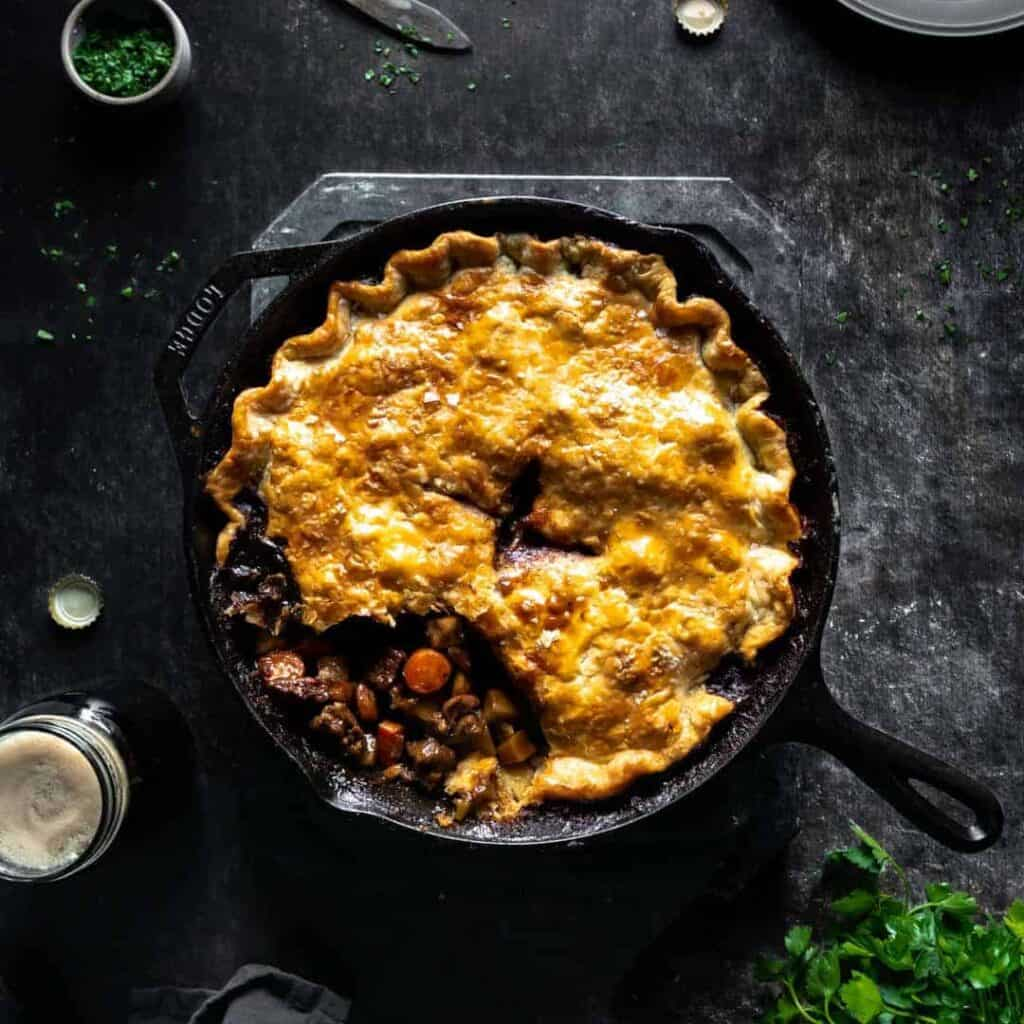 A stout braised lamb pie in a skillet with a scoop of pie crust missing