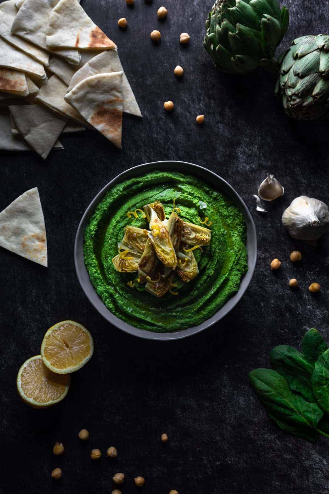A big bowl of bright green spinach hummus topped with artichokes and surrounded by chickpeas, spinach, artichokes, a halved lemon and several triangles of pita bread