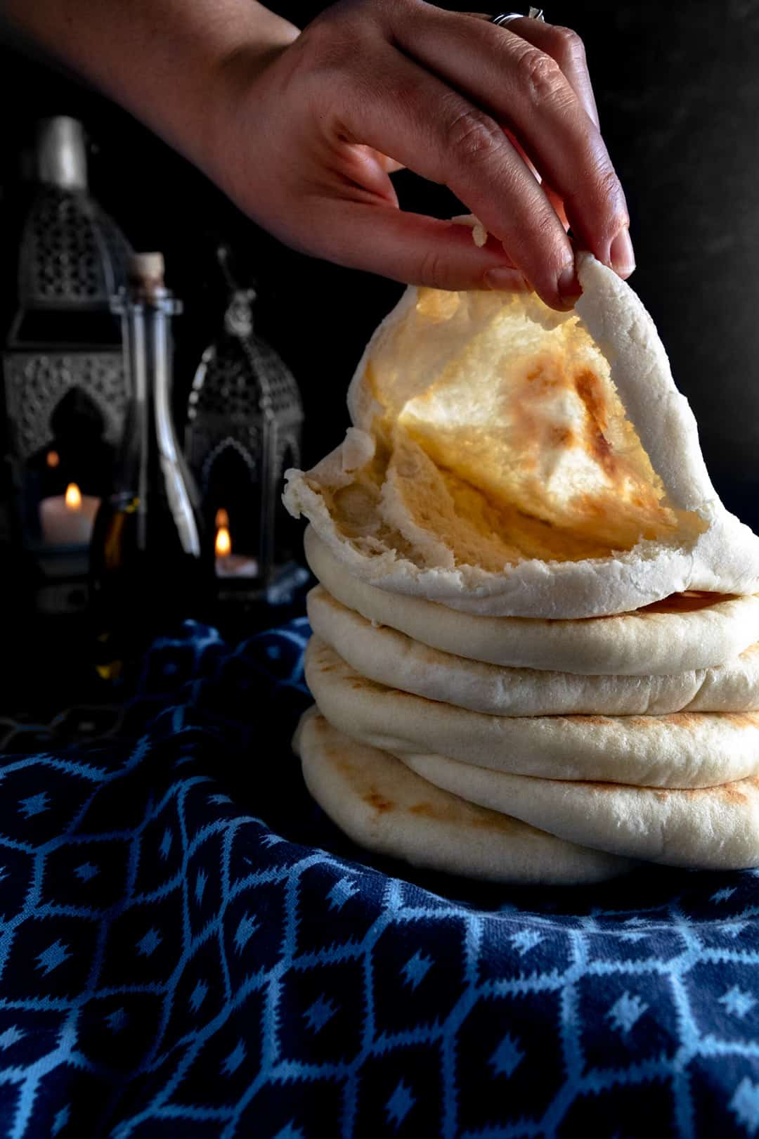 A stack of freshly baked pita bread on blue linen with the top one ripped and held open with a hand to reveal the perfect pocket. Candle lanterns are lit in the background.