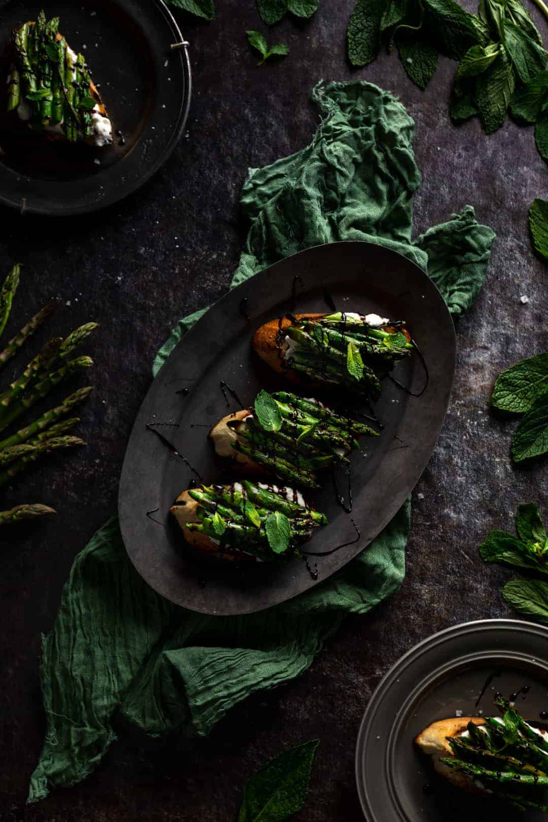 An oval tray on a green linen topped with 3 pieces of grilled asparagus and whipped ricotta toast. Two plates with additional toasts sup pound the platter with stalks of raw asparagus and fresh mint leaves