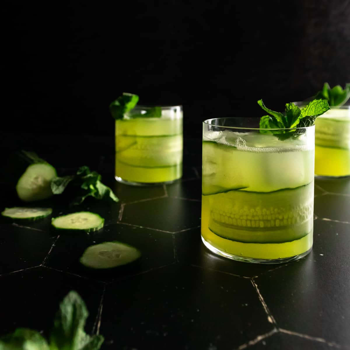 Three rocks glasses filled with cucumber mojitos garnished with a cucumber ribbon in the glass and a fresh mint sprig. A sliced cucumber and bunch of mint is in the background