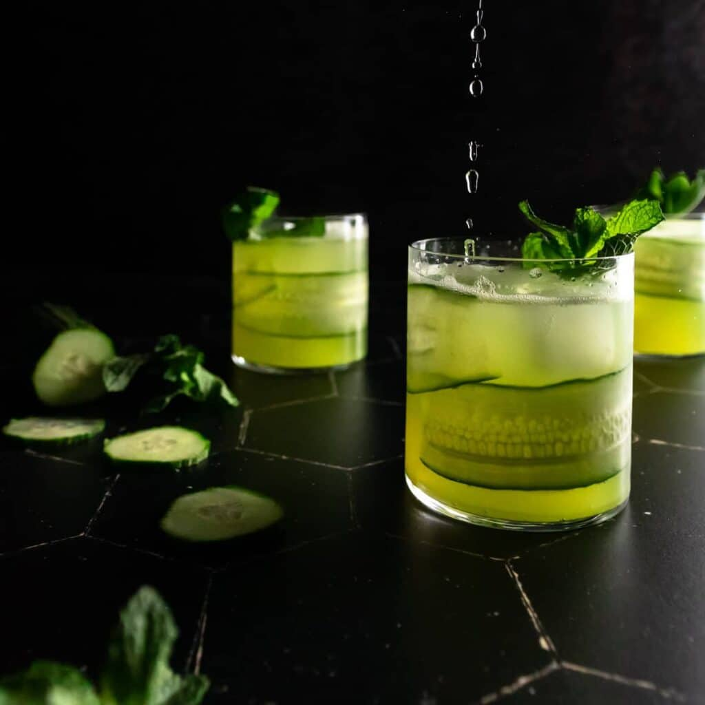 the last drops being poured into one of three cucumber mojito cocktails surrounded by fresh mint leaves and sliced cucumber