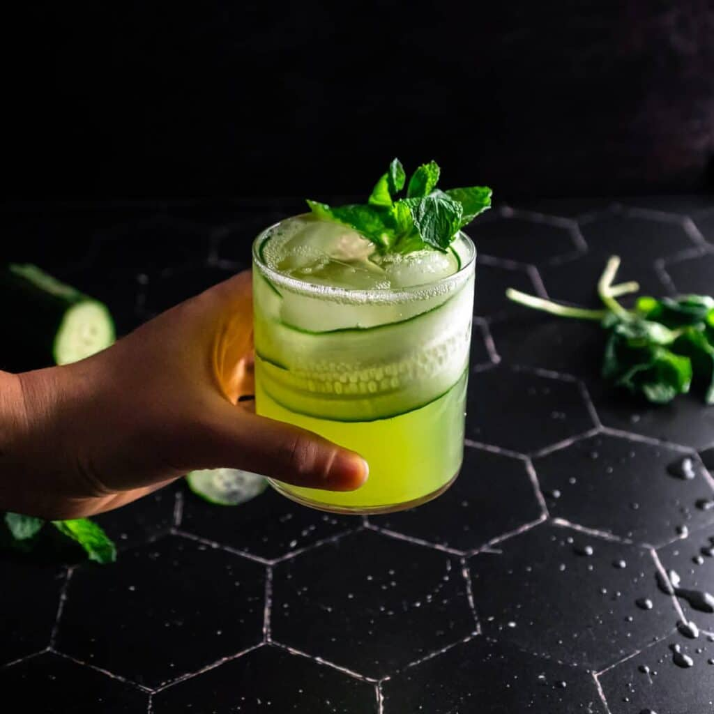 A hand holding a cucumber mojito