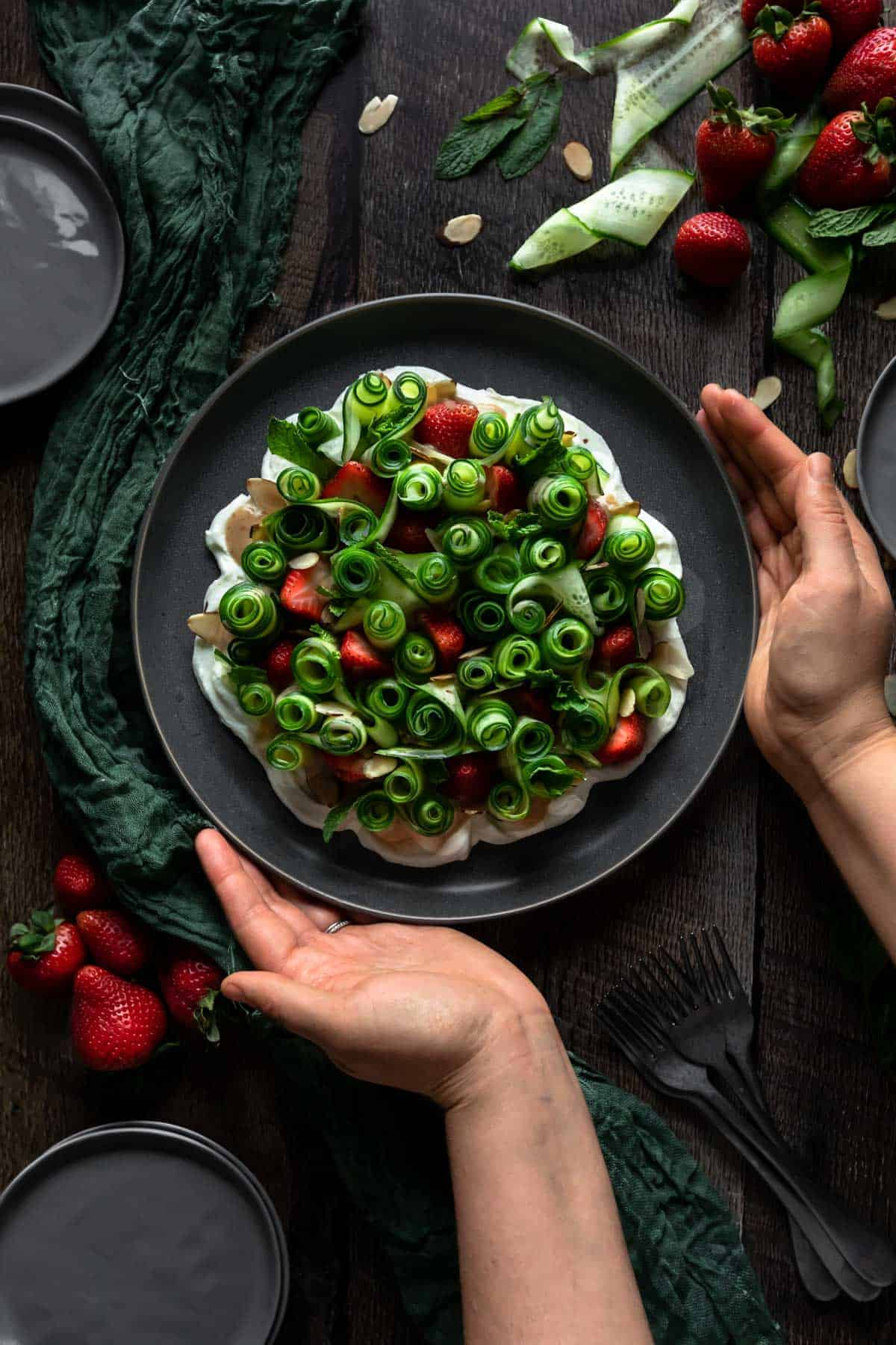 Two hands placing down a plate of curled cucumber ribbon salad with fresh strawberries and toasted almonds on a bed of whipped goat cheese. A green linen, forks, plates, and additional strawberries and slices of cucumber surround the plate.