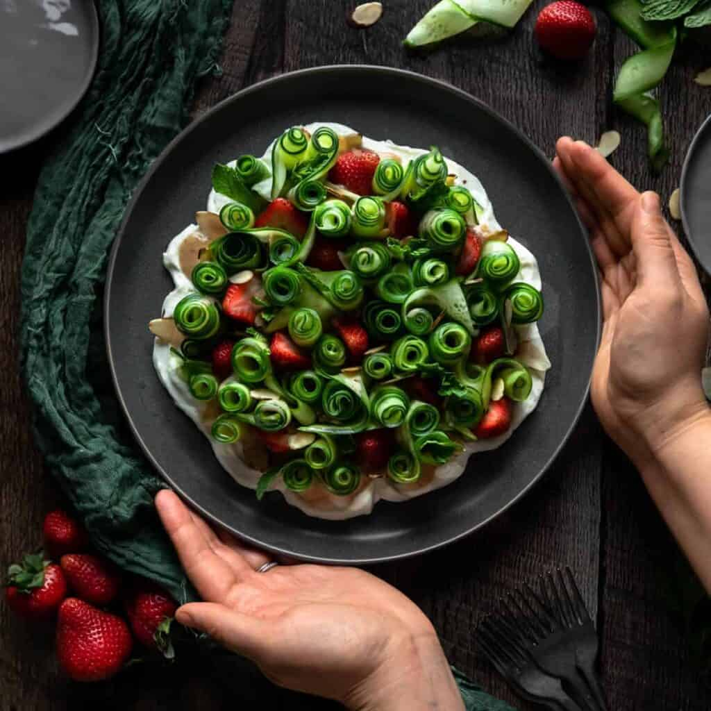 Cucumber ribbon and strawberry salad served on a bed of whipped goat cheese on a grey plate. The plate is being placed down with two hands onto a table with a green linen and fresh strawberries