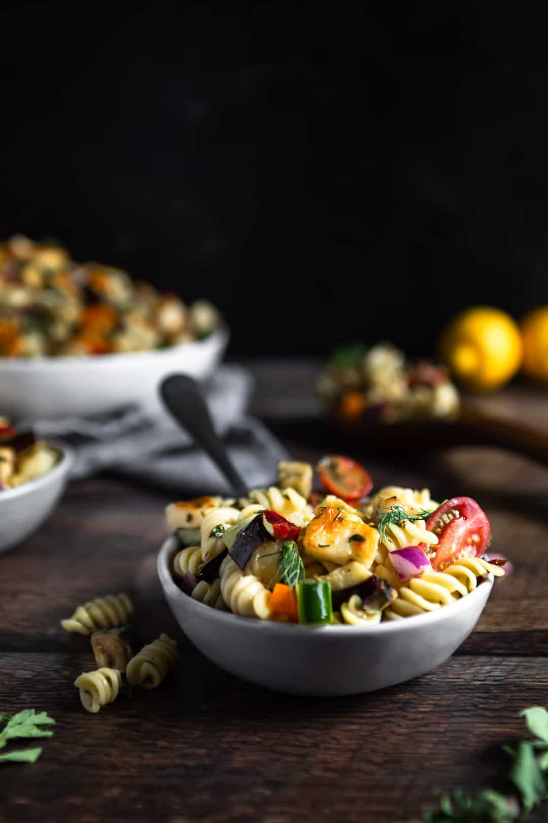 A small dish filled with Halloumi pasta salad with a fork in it and a few rotini that fell out beside the dish. A large serving bowl of the pasta salad and lemons are in the background