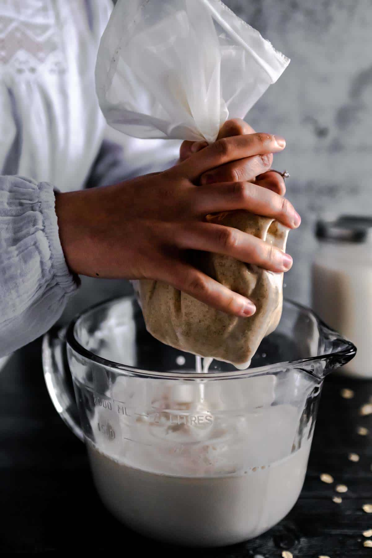 A woman gently squeezing oat milk through a nut bag and into a large glass mixing bowl