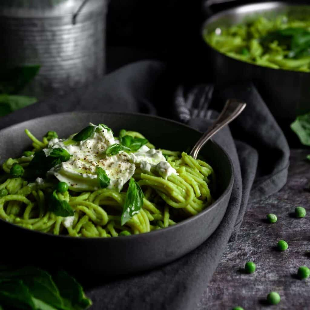 Bowl of Green Pea Pasta topped with burrata cheese