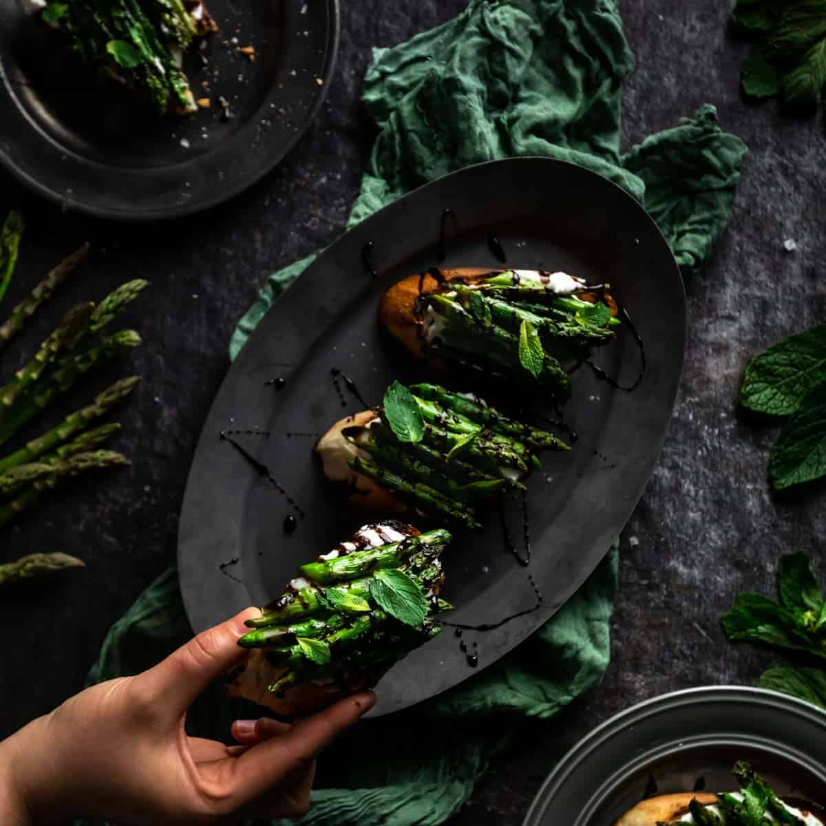 A hand reaching for a Whipped Ricotta & Grilled asparagus toast