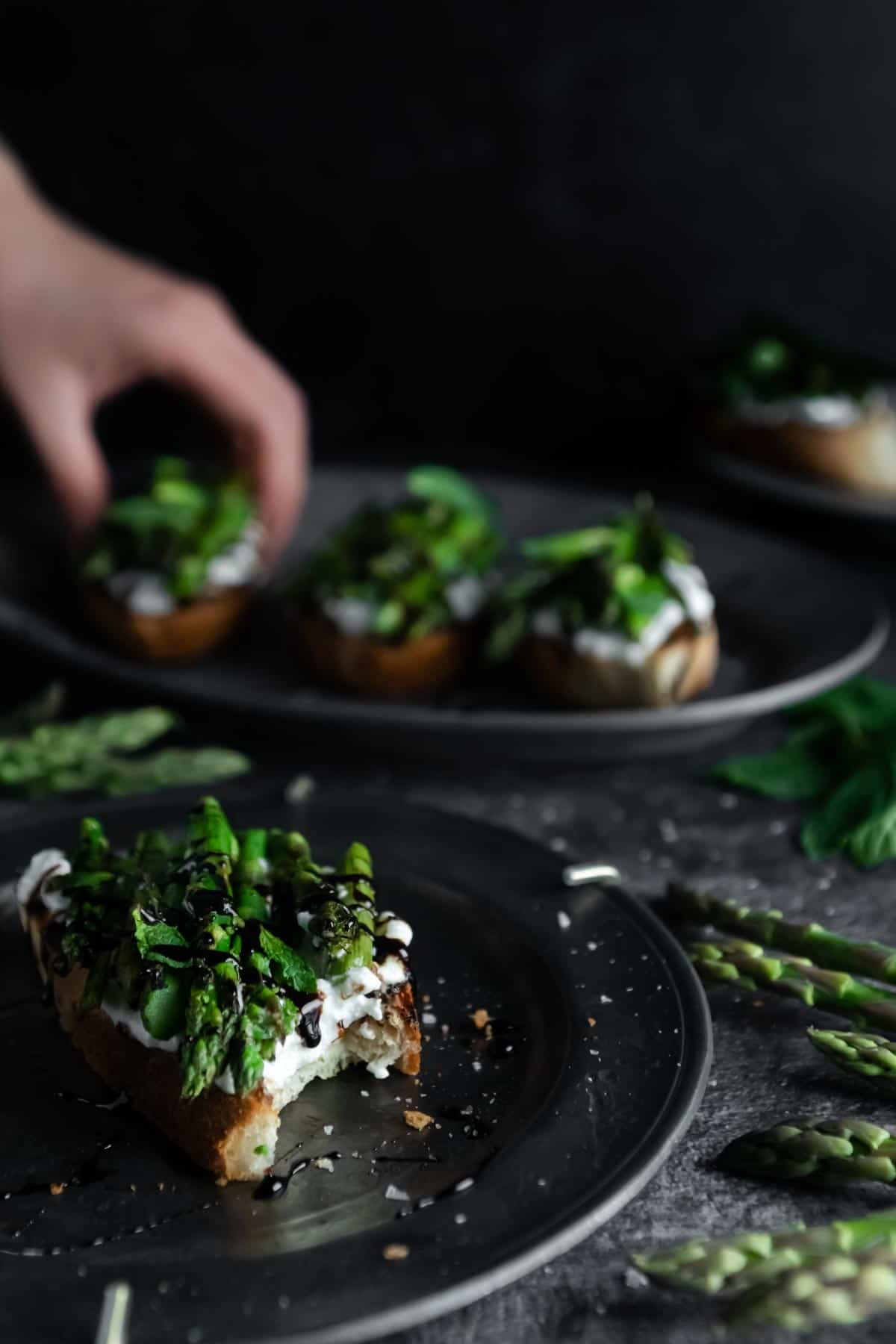 A bite shot revealing creamy Whipped Ricotta layered with grilled asparagus and balsamic glaze