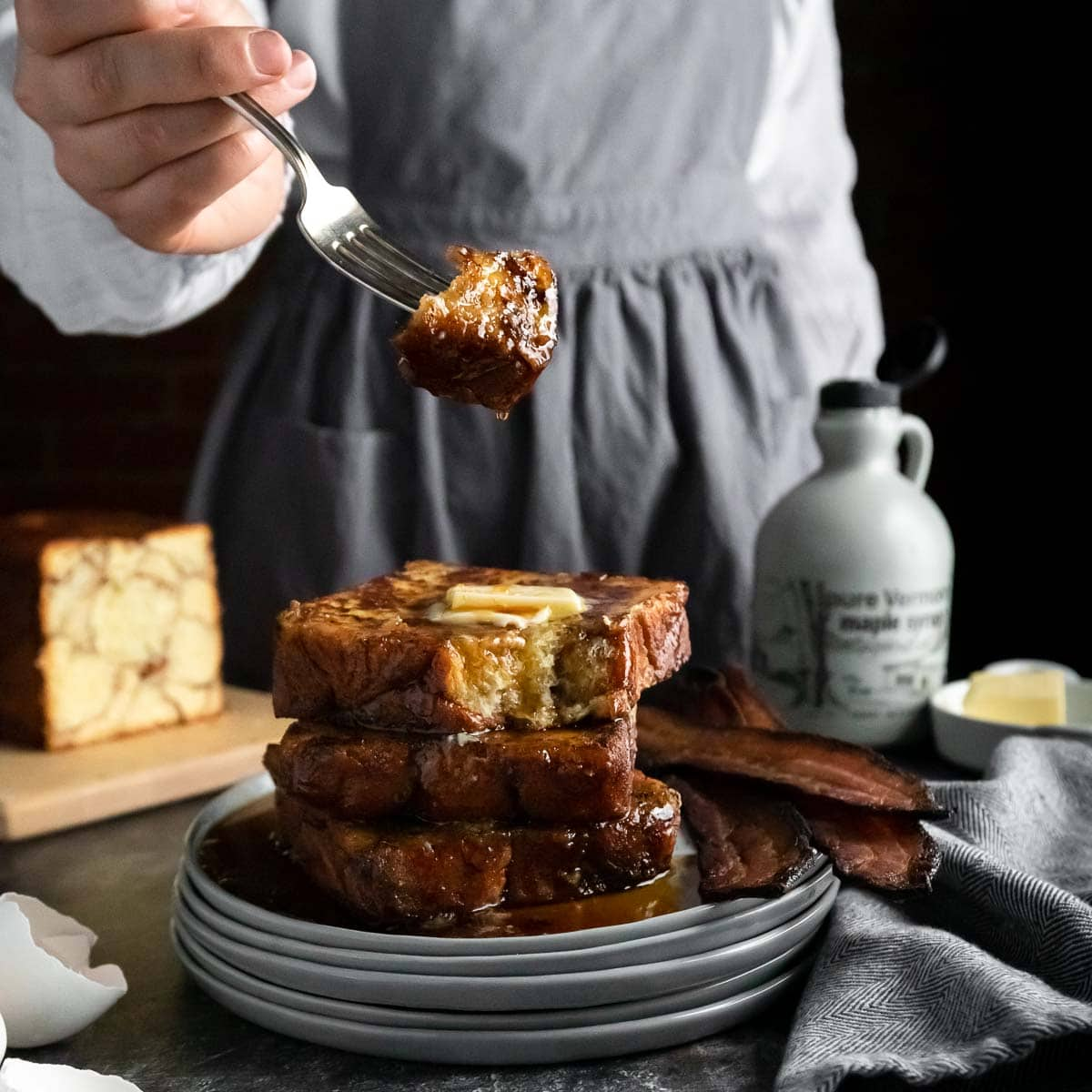 A bite of Monkey Bread French Toast on a fork being held above a tall stack of French toast