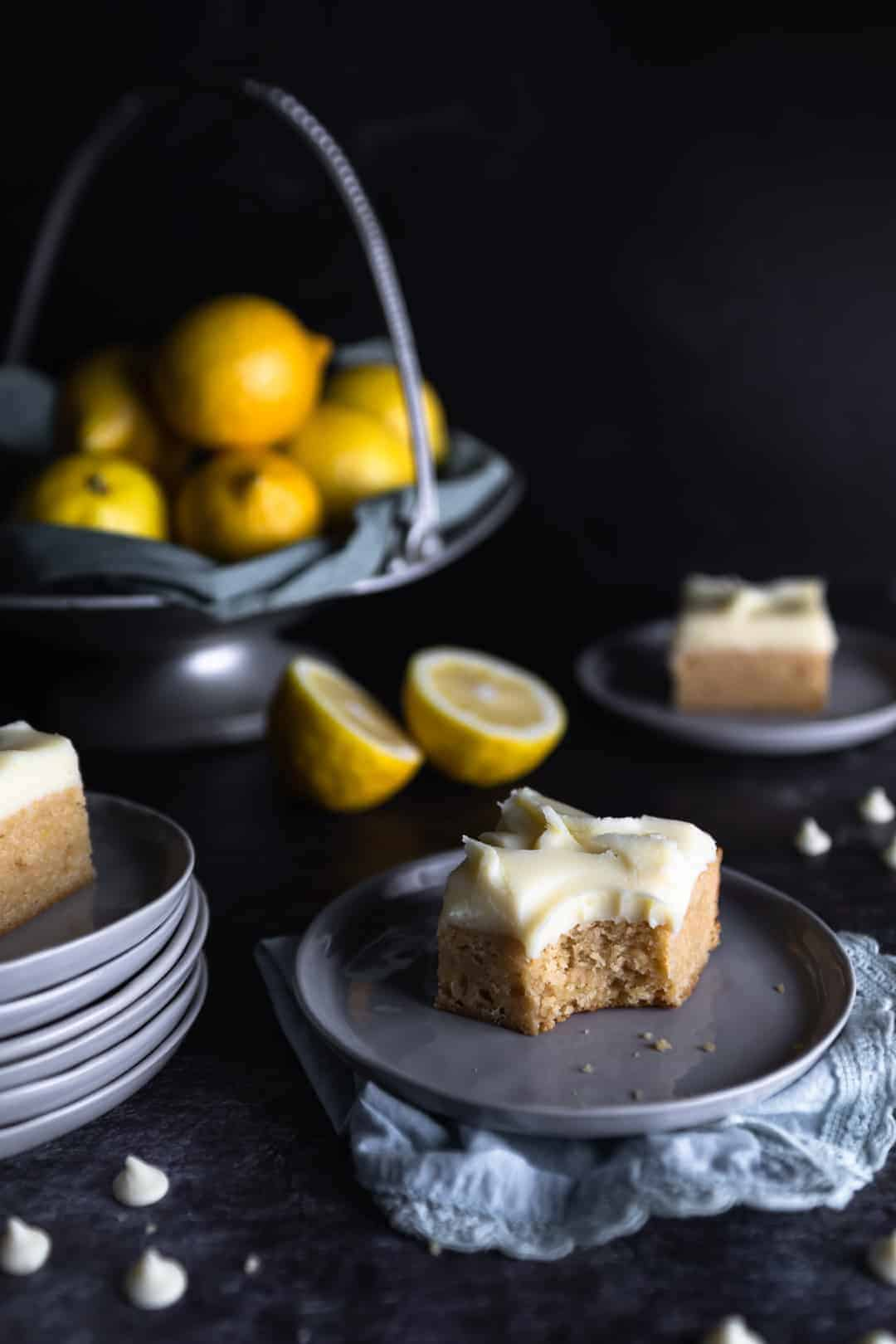 A lemon blondie with white chocolate ganache frosting on a small plate with one bite taken out. Two other blondies are on small plates nearby, white chocolate chips are scattered around and a big bowl of lemons are in the background