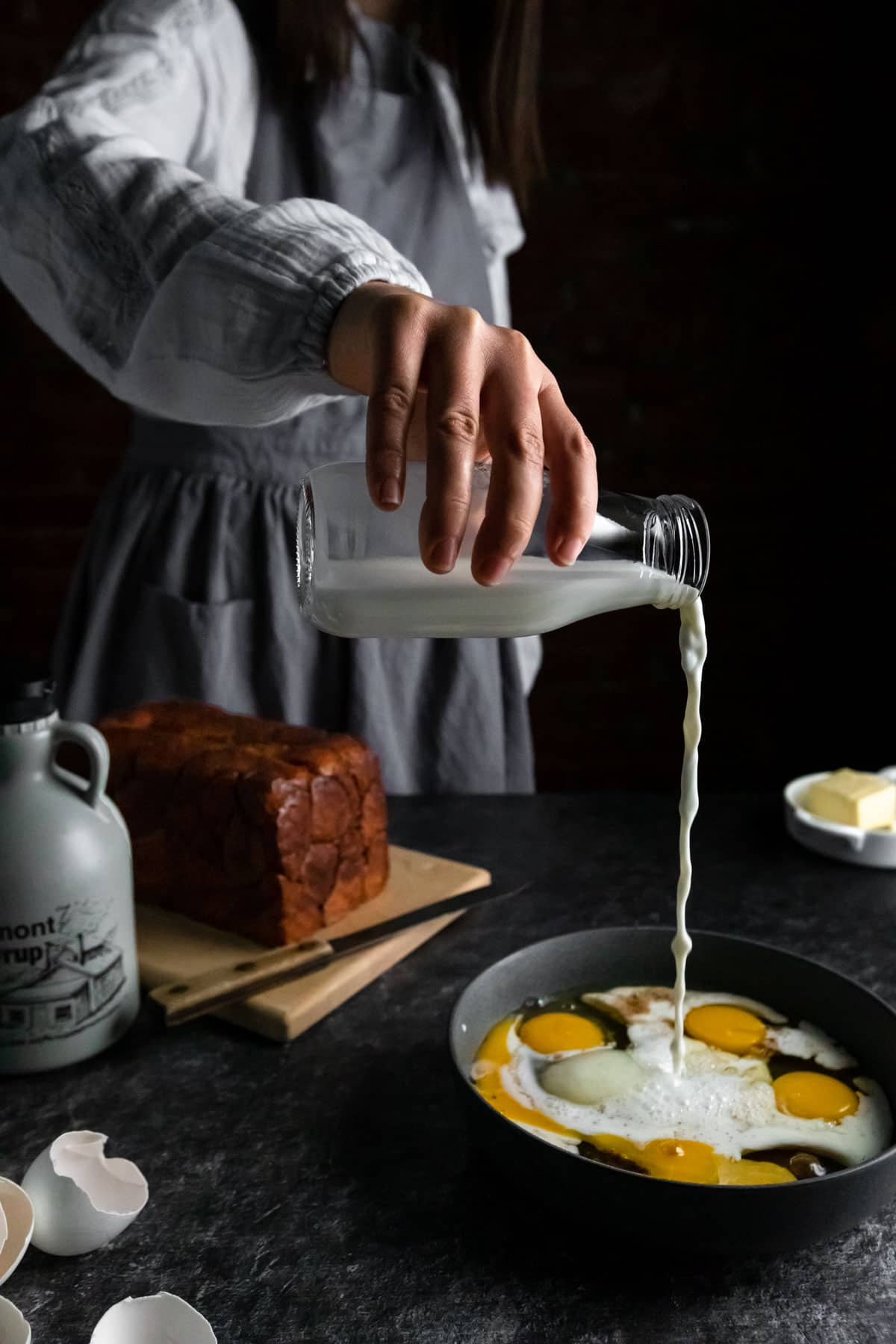 An aproned woman pouring the milk from an old fashioned glass jug into a bowl of eggs to make the French Toast Batter. A loaf of Monkey Bread on a cutting board, cracked egg shells and a jug of maple syrup are on the table.
