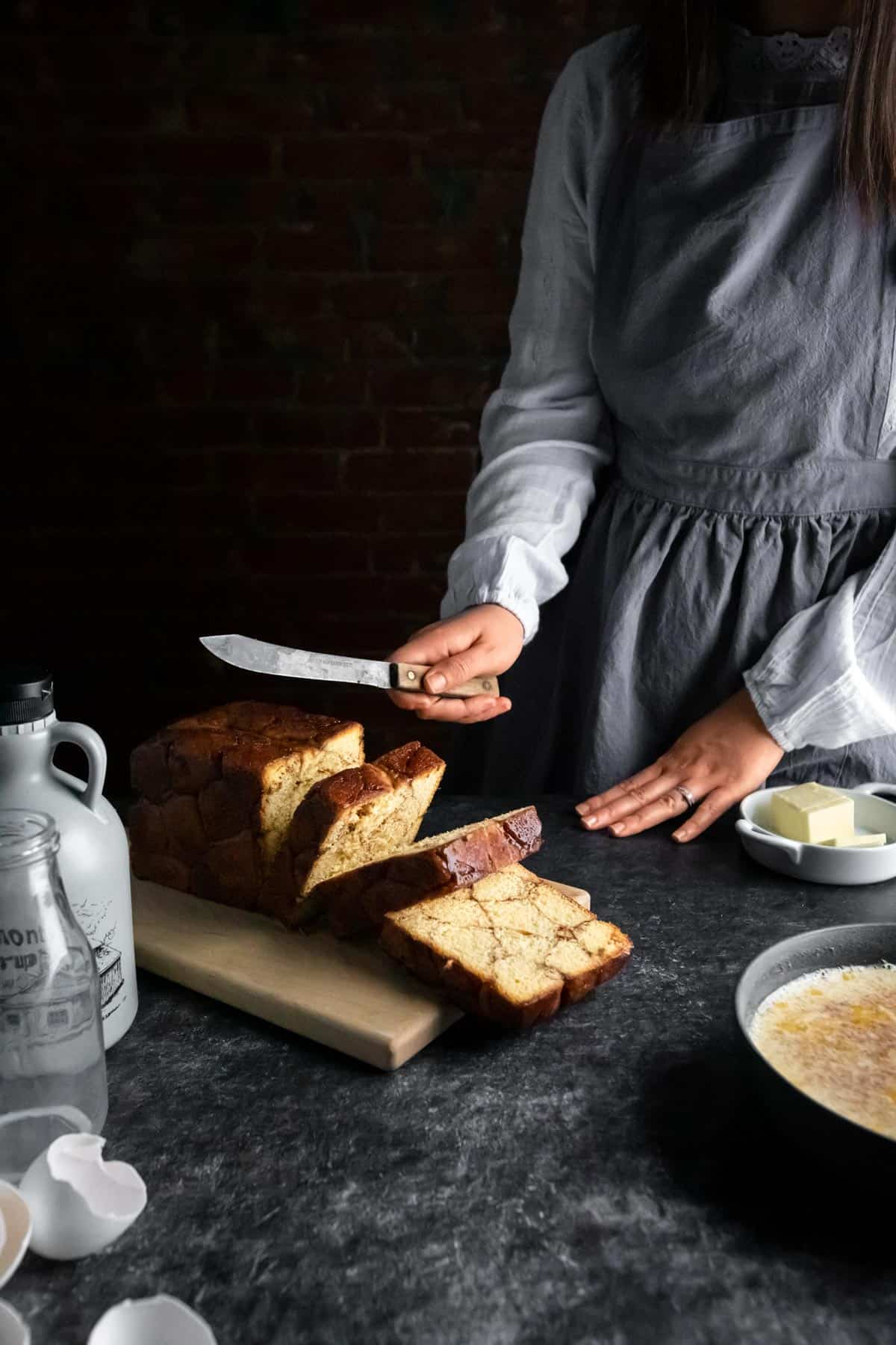 A woman Slicing the Monkey Bread Pullman Loaf with an old knife. A bowl of French Toast batter, cracked egg shells, a jug of maple syrup and butter are on the table.