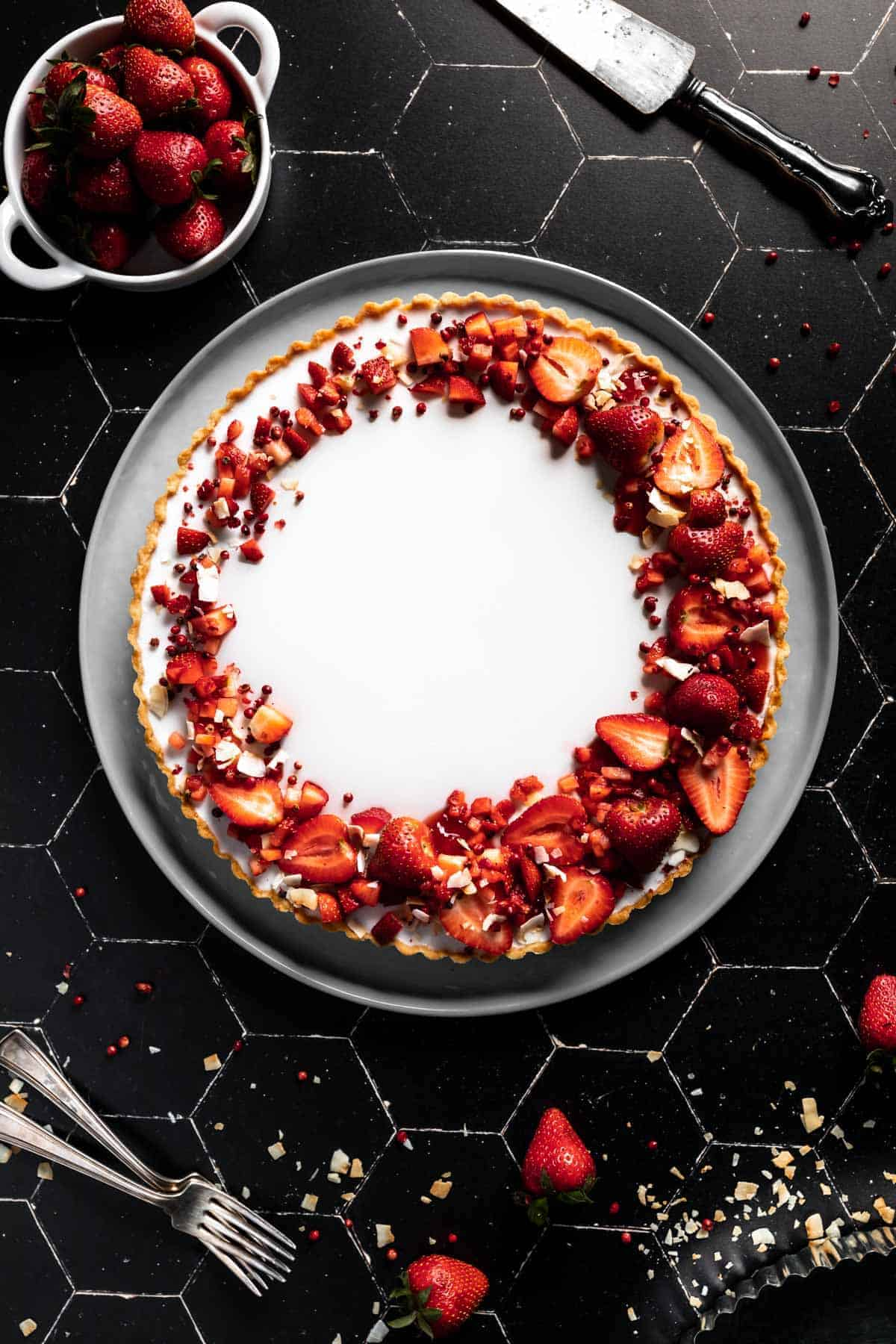 overhead shot of a Coconut Tart with a crescent design of Strawberries. Next to the Panna Cotta tart is flakes of toasted coconut, a bowl of strawberries, a serving utensil and two forks