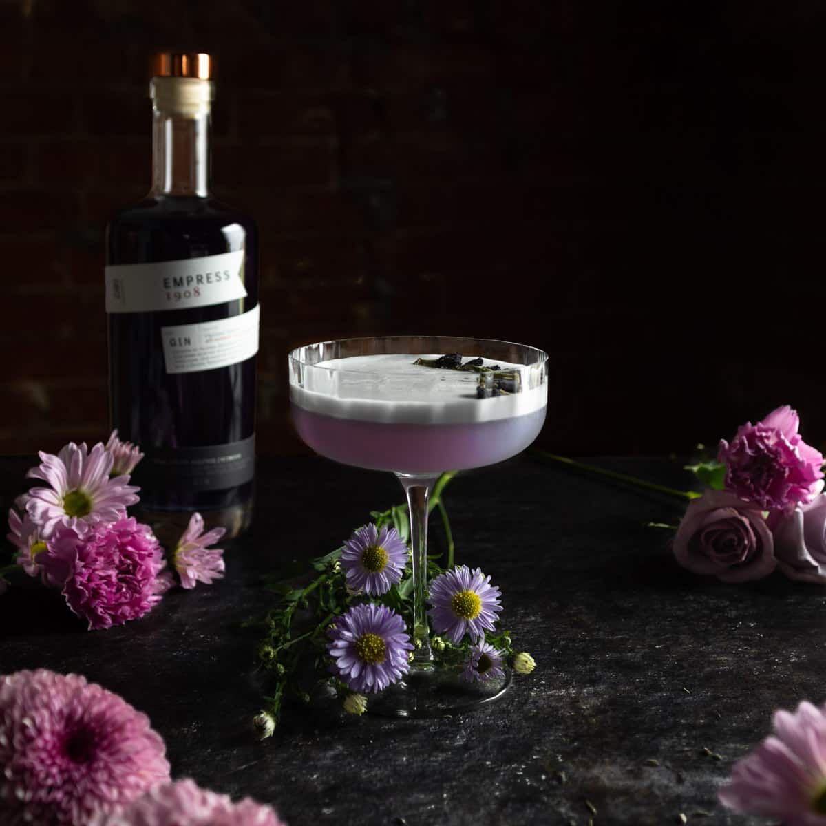 A lavender gin sour next to a bottle of Empress 1908 gin surrounded by purple flowers