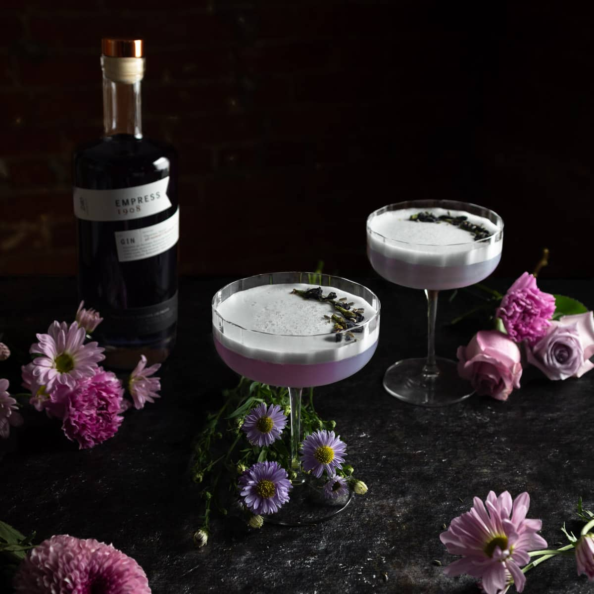 Empress 1908 Gin sour Cocktails surrounded by fresh purple flowers and a bottle of Empress gin