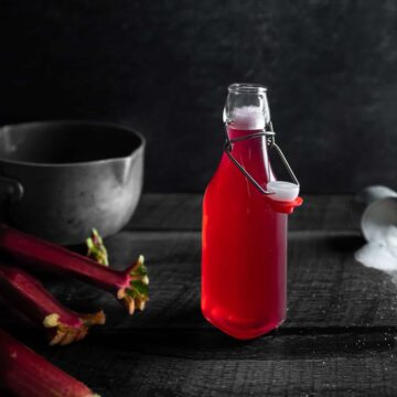 Bottle of bright pink Rhubarb Syrup