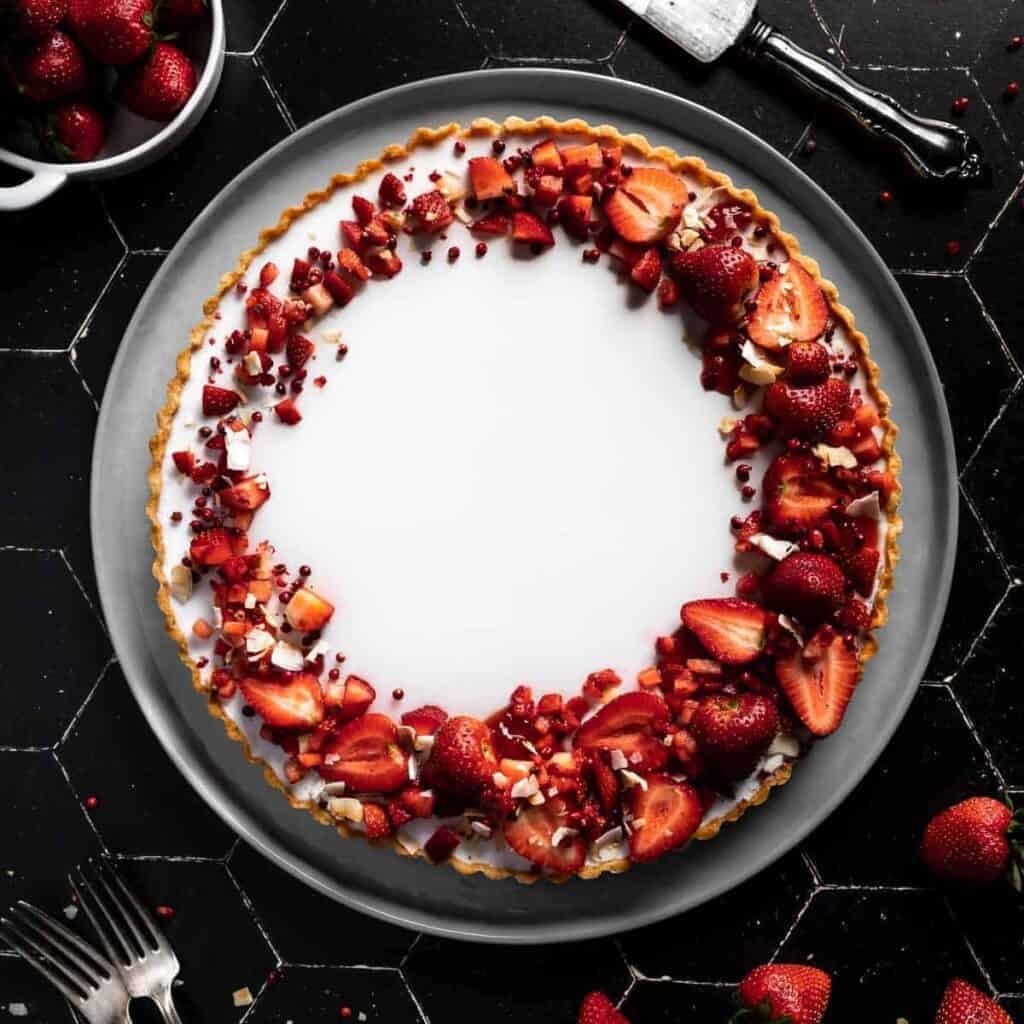 overhead shot of a Coconut Tart with a crescent design of Strawberries
