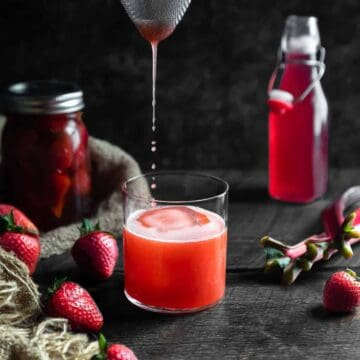 Strawberry Whiskey Sour Being poured into a glass through a strainer. The glass is surrounded by a jar of strawberry infused whiskey, fresh strawberries and a bottle of rhubarb syrup