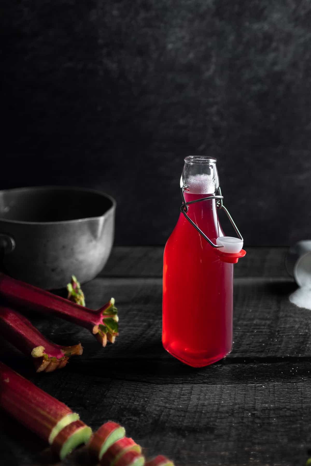 A small bottle of bright pink rhubarb syrup with a pot in the background next to s spilled cup of sugar and a stalk of chopped rhubarb