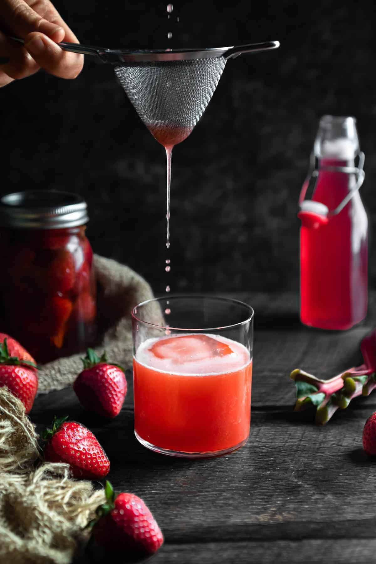 The last drops of a Strawberry Rhubarb Whiskey Sour being poured through a tea strainer into a rocks glass. A jar of strawberry infused whiskey with a burlap cloth, fresh strawberries and a bottle of rhubarb syrup are in the background.