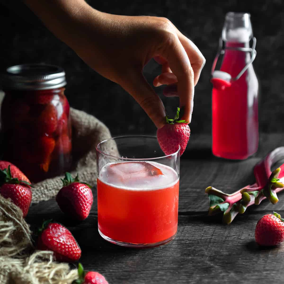 Placing a strawberry on a strawberry rhubarb whiskey sour