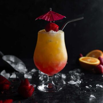 Strawberry Rose Tequila Sunrise garnished with an umbrella