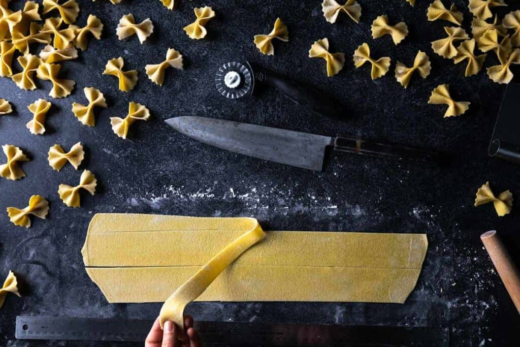 A hand pulling a way a scrap of semolina pasta dough away from a squared edge