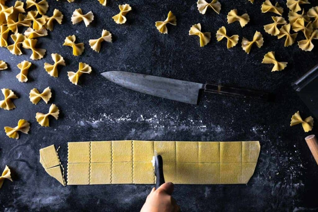 A fluted pastry wheel cutting squares of pasta dough