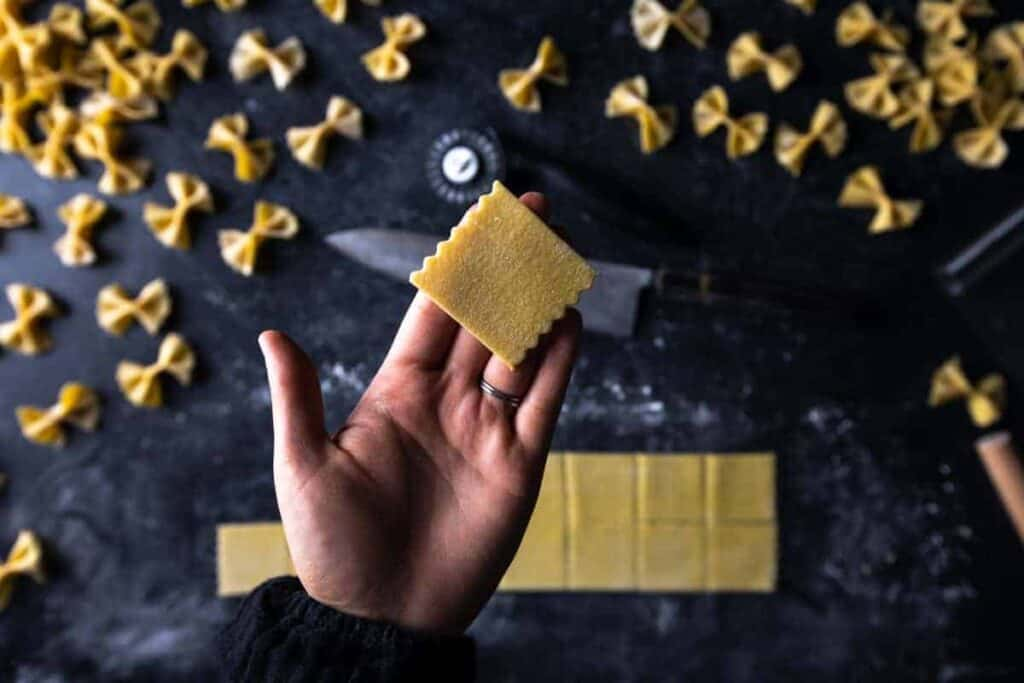 a hand holding up a square with parallel fluted edges to use for farfalle pasta