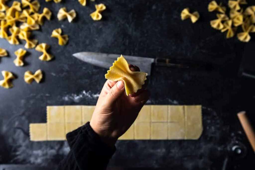 a hand pinching a square of pasta dough into a bowtie shape
