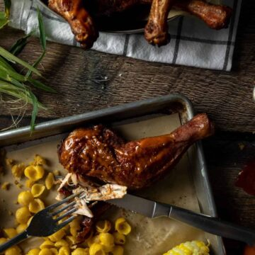 A fork and knife tearing off a piece of BBQ rubbed smoked chicken quarter on a tray next to Mac and cheese and corn on the cob