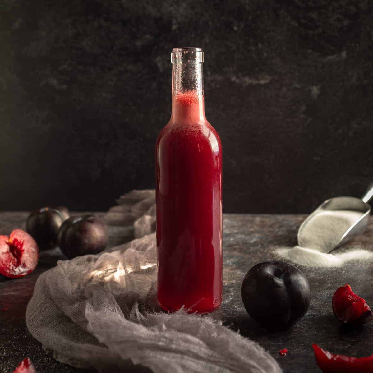 a skinny bottle of purple plum syrup surrounded by fresh sliced plums with a scoop of sugar in the background