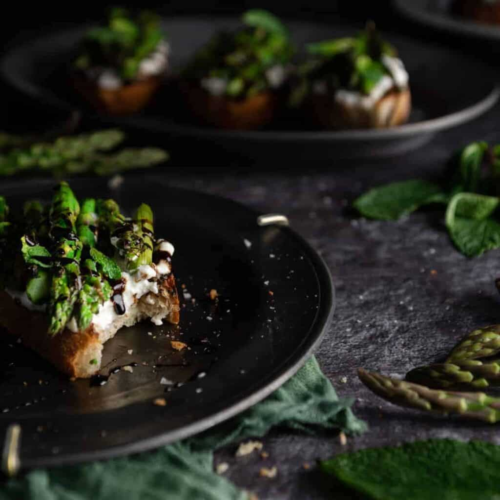 A bitten piece of toast topped with asparagus, ricotta cheese and balsamic glaze