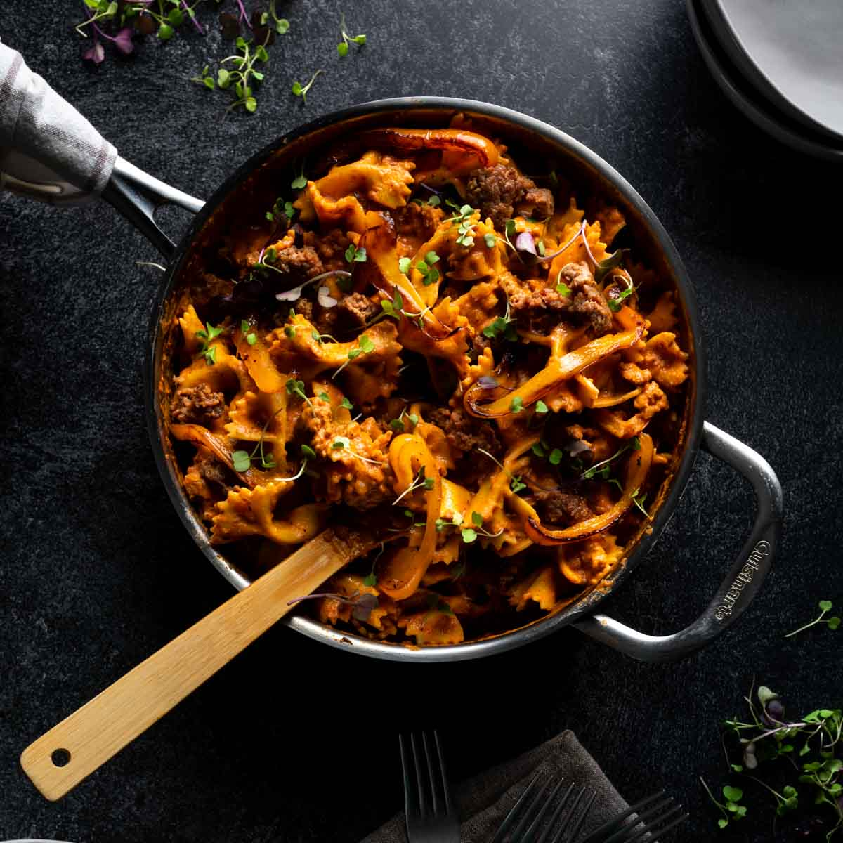 A skillet full of creamy cajun style farfalle pasta with andouille sausage that has a wooden spoon in it and a sprinkle of spicy micro greens on top